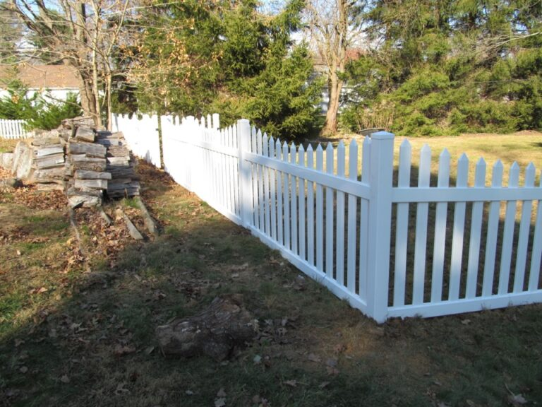White picket fence and woodpile