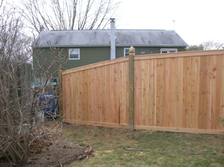 Wooden Panel Fence in front of Green House